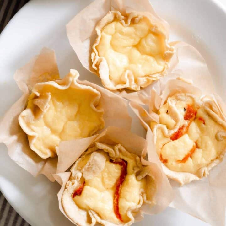 overhead photo of four mini quiches: two just plain with cheese, and two with roasted red pepper and onion) on a white plate