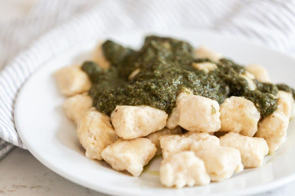 homemade pesto poured on top of gnocchi on a white plate.