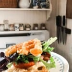 close up picture of a BLT made with sourdough cheddar waffles as the bread. The sandwich is on a white plate