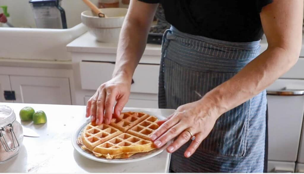 women wearing a blue stripped apron placing a cheddar waffle on a white plate on her white kitchen island