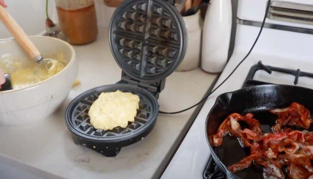 sourdough cheddar waffle batter in a waffle iron with a cast iron skillet full of bacon to the right.