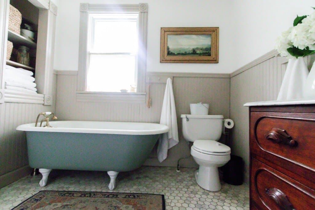 blue green antique clawfoot tub in a 1800s farmhouse bathroom. A toilet with art hanging above it sits to the right of the tub