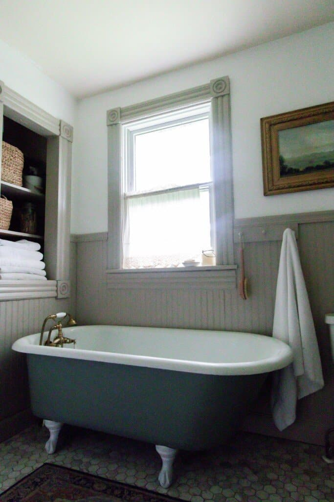 clawfoot tub in a 1800s farmhouse with bead board lined walls and a build in shelves behind the tub