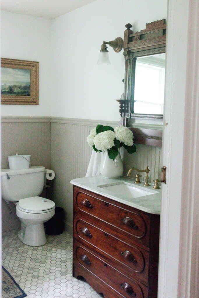 side view into the farmhouse bathroom renovation with antique dresser with marble vanity