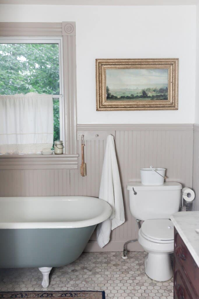 Farmhouse bathroom renovation with printed art in a antique frame over a toilet