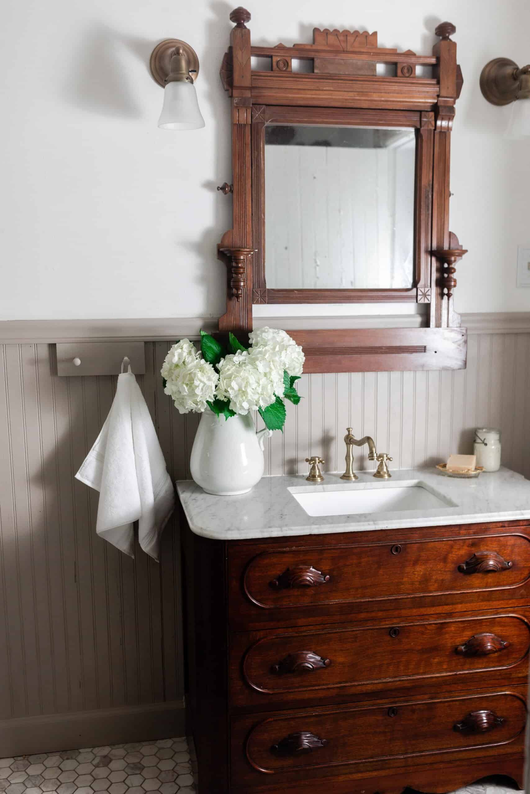 Antique dresser turned into a vanity with a marble tub with a ornate wood mirror. Bead board graces the walls and antique accessories