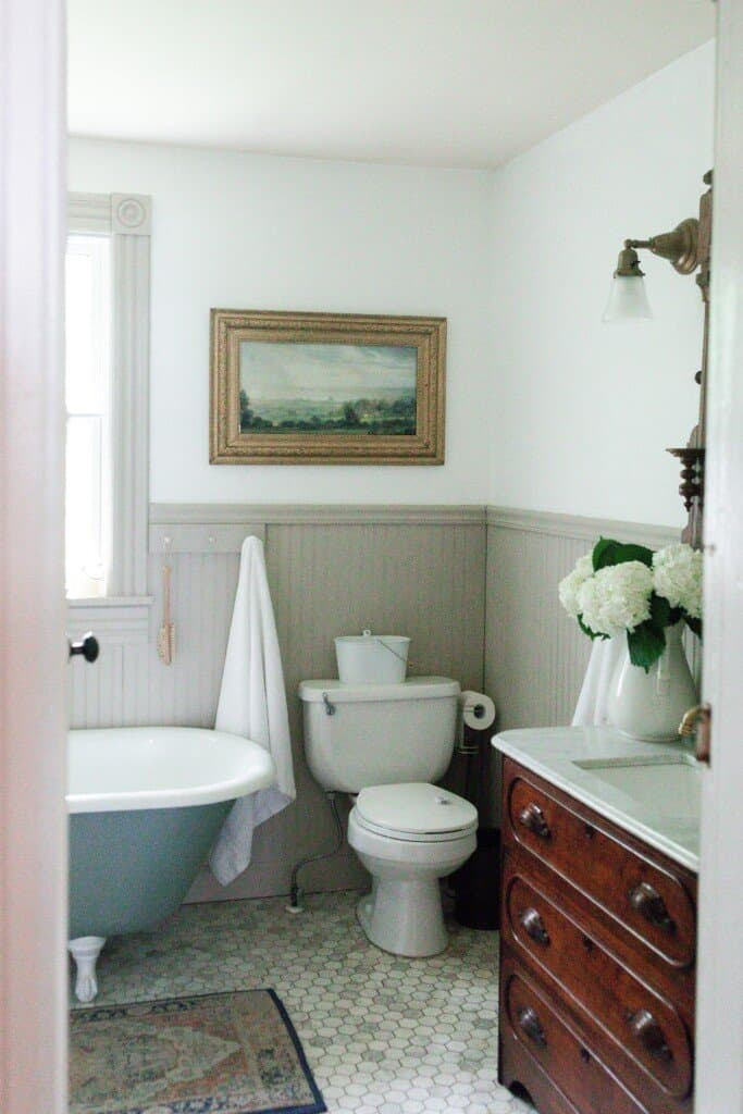 Farmhouse bathroom renovation with marble floors, a blue green clawfoot tub, and vintage dresser turned sink