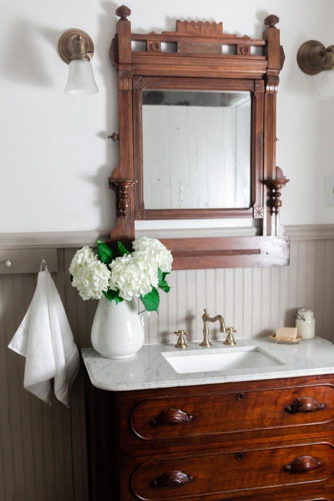 wood antique dresser with a marble top and sink  with a vase of hydrangeas.A wooden antique mirror hands above the vanity with lights on each side of the mirror