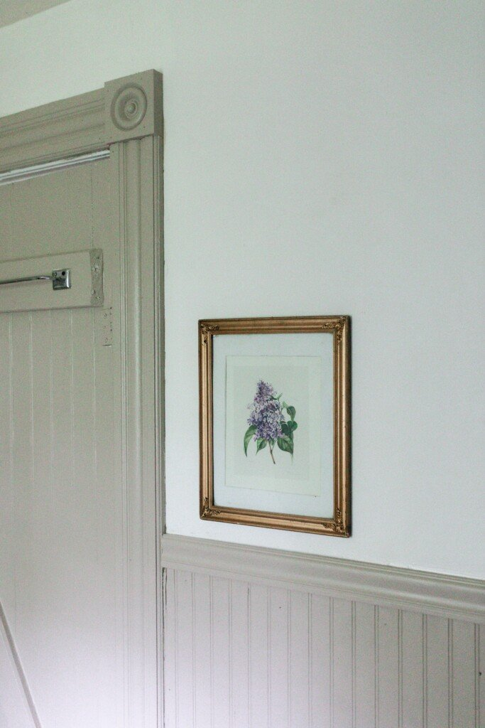 Art hanging in a antique gold frame above beige bead board with a chair rail