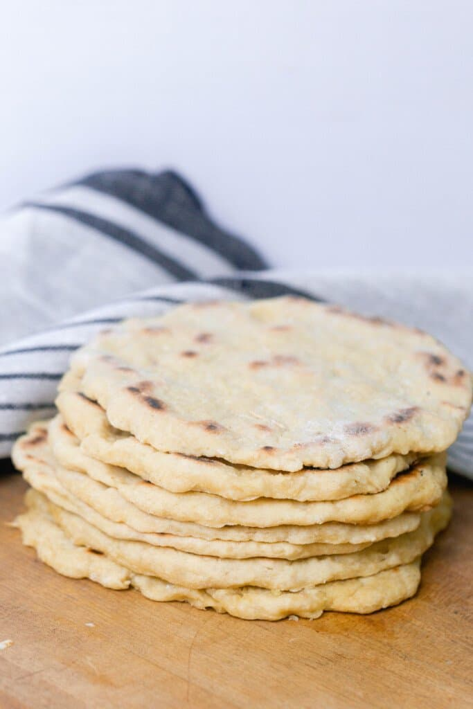einkorn flat bread stacked on a wood cutting board 7 high with a black and gray stripped towel in the background