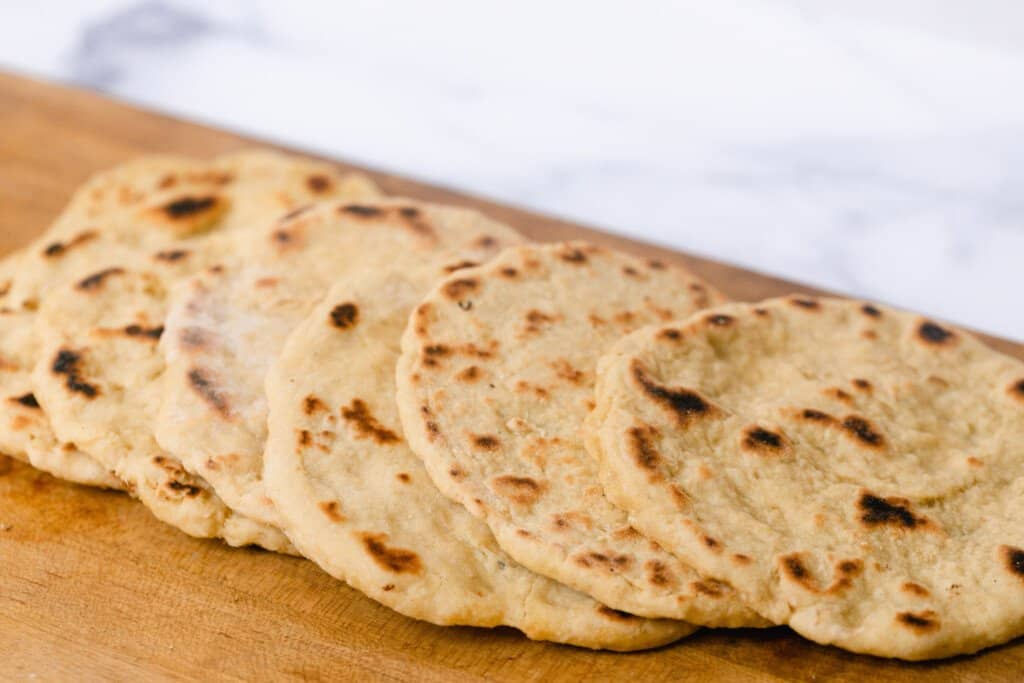 einkorn flat breads spread out in a row on a wooden cutting board