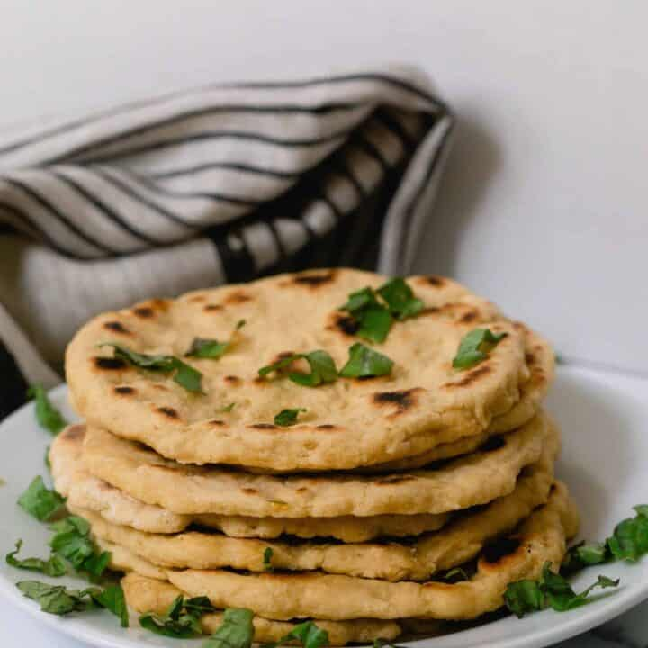 einkorn flat bread stacked with herbs sprinkled over on a white plate with a gray and black stripped tea towel in the background