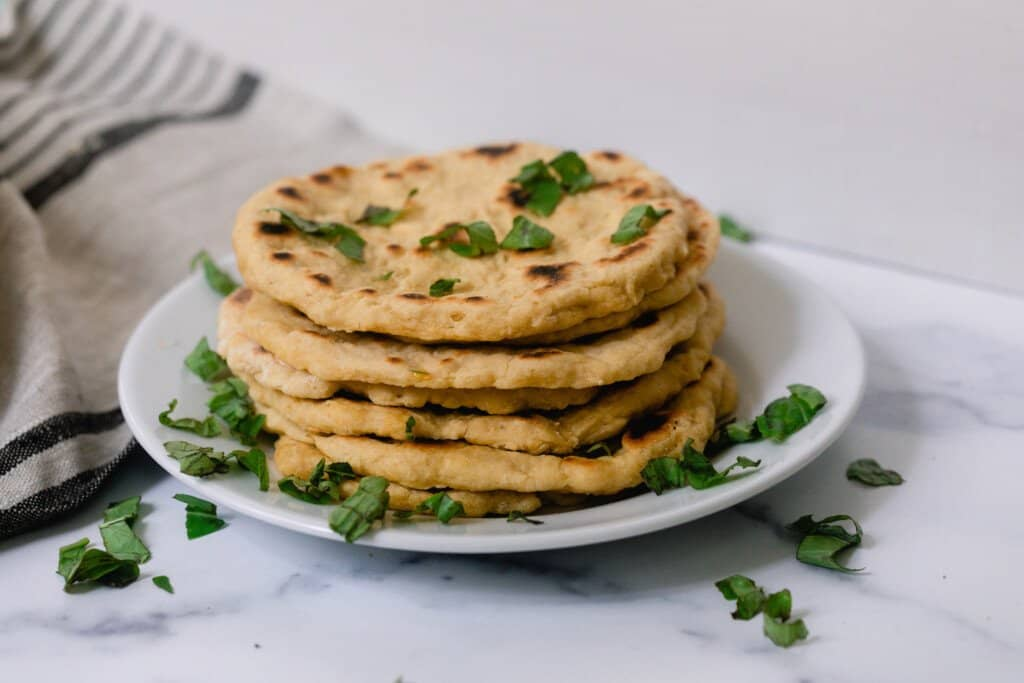 stack of einkorn flatbread with herbs on a white plate on a white and gray quartz countertop