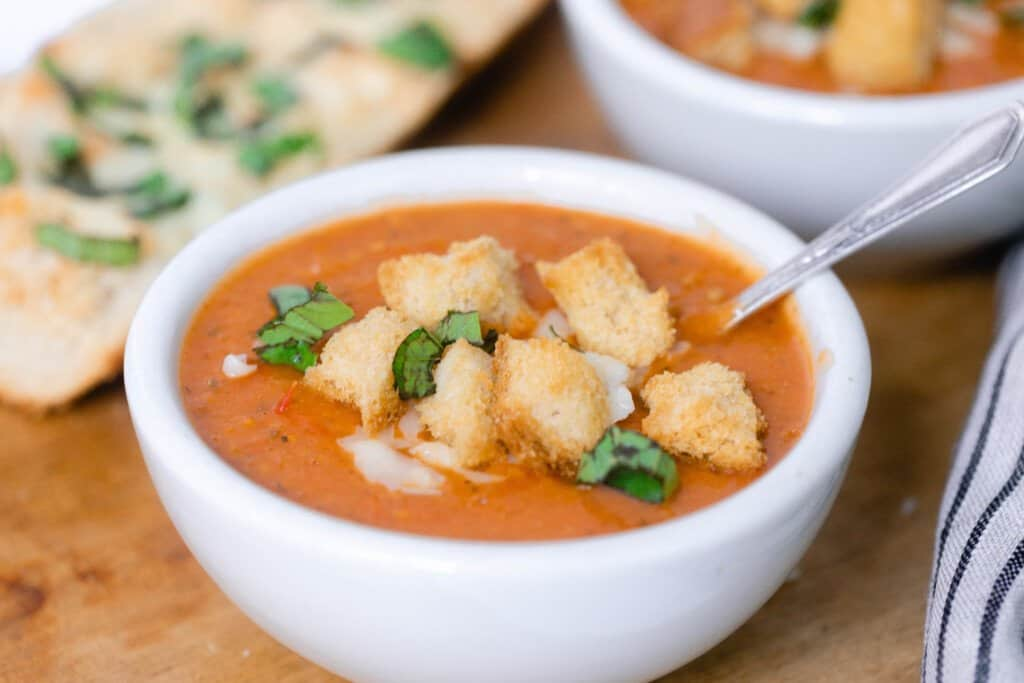 close up picture of a white bowl full of tomato soup with homemade croutons, fresh basil, and cheese in a bowl on a wood cutting board