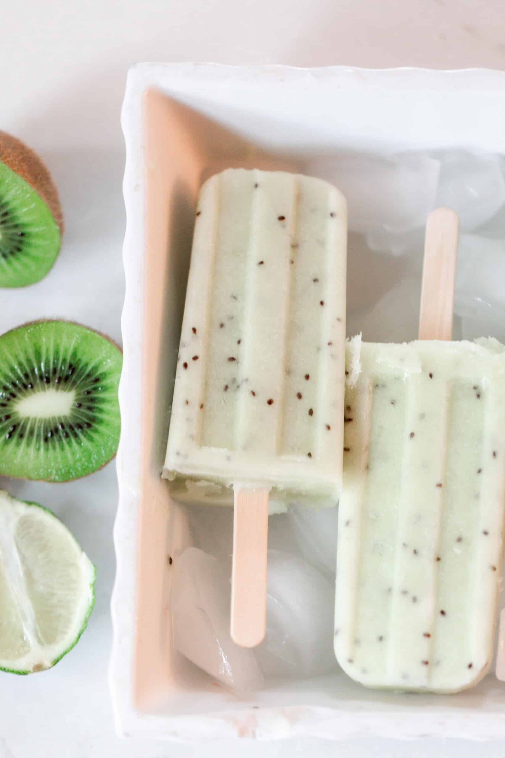 two kiwi lime popsicles in a white dish with ice. Halved kiwis and a lime sit to the left of the dish