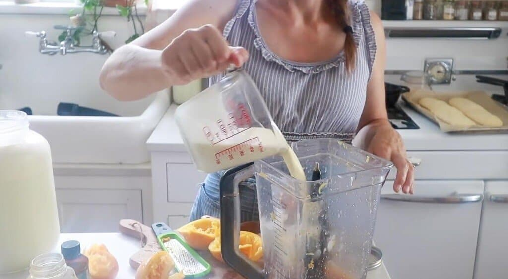 women pouring milk and cream into a blender to make popsicles