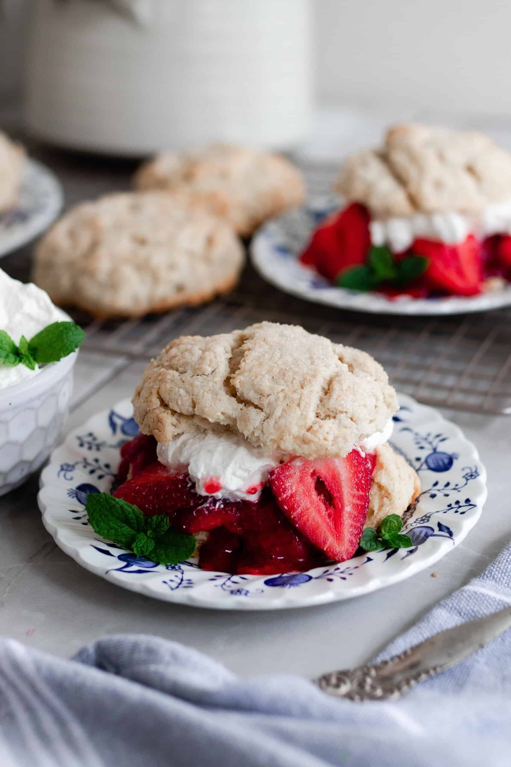 two strawberry shortcakes with whipped cream and strawberries layered between the biscuits on a white and blue plates with extra biscuits and whipped cream behind the plates