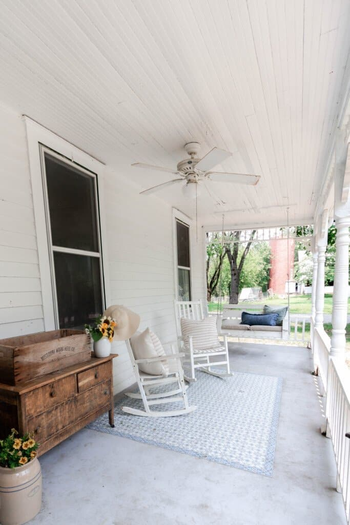 summer farmhouse front porch complete with an antique dresser with a vase of sunflowers, two white rocking chairs, and a porch swing