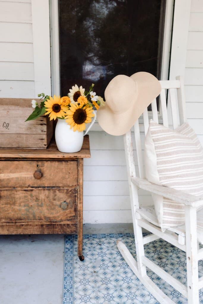 antique dresser on a front porch with a vase of sunflowers. A rocking chair with a stripped pillow and a hat sitting on top of a blue rug is placed to the right of the dresser