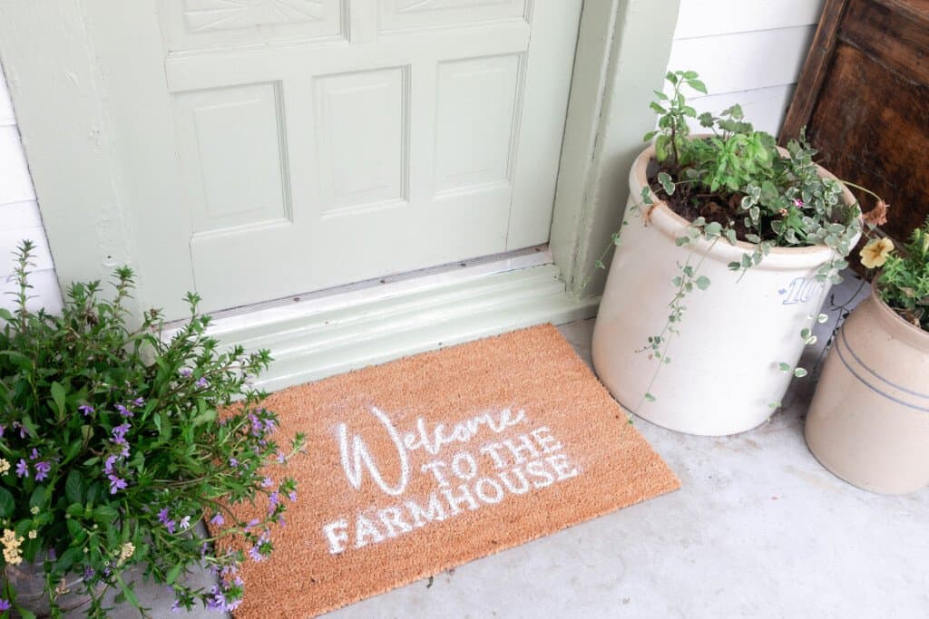"""""""Welcome to the farmhouse"""" doormat in front of a sage green antique door with a antique crock full of flower to the right"""