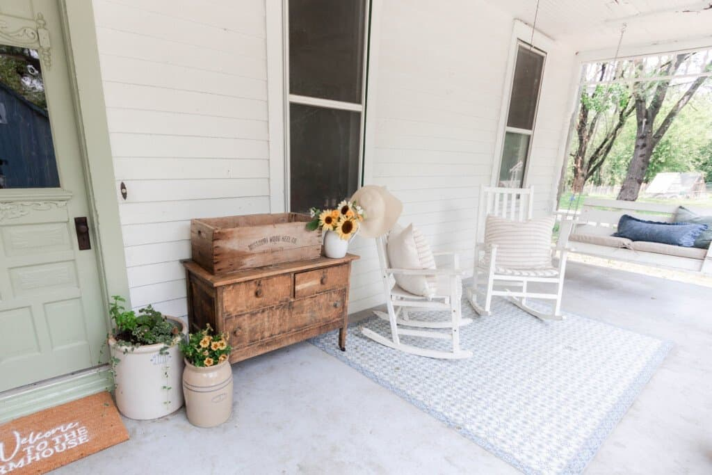 White farmhouse front porch with a sage green door and custom doormat. Antique furniture and white rocking chairs finish off the space