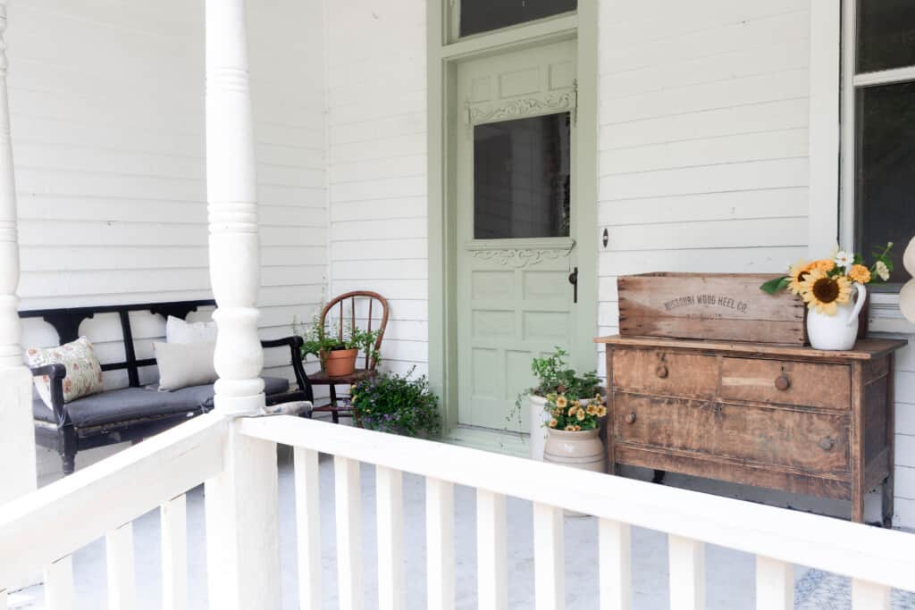 farmhouse front porch with a sage green door, with a antique dresser to the right and a black antique chair to the left