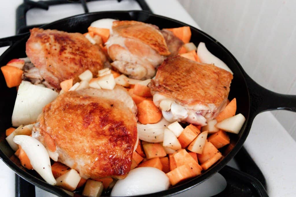 sweet potatoes, apples, and onions arranged around a four browned chicken thighs