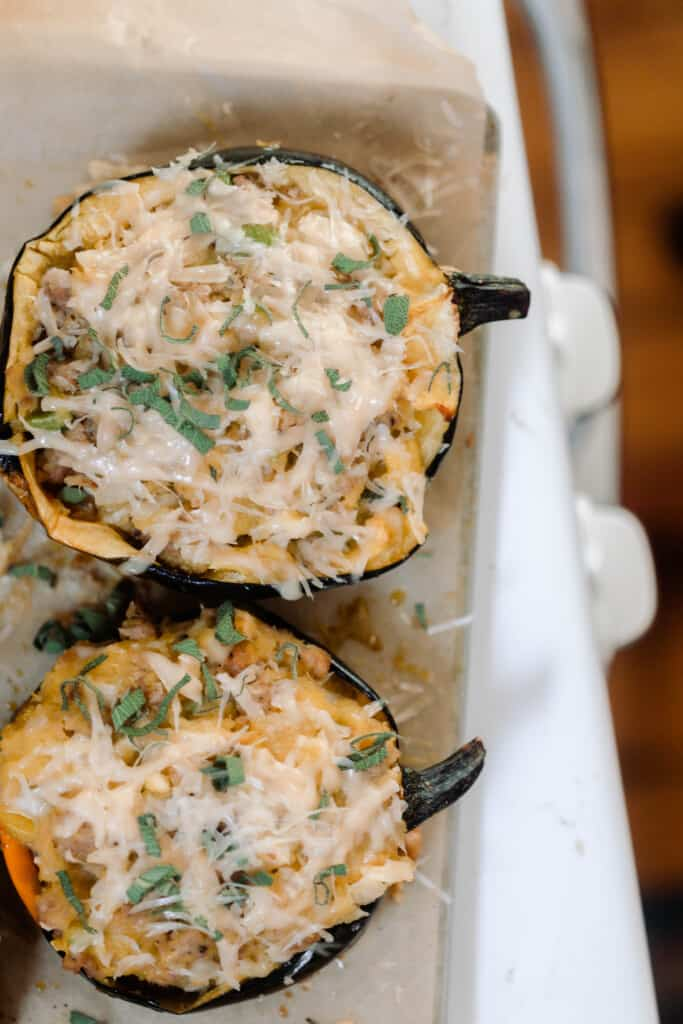 overhead photo of two halved acorn squashes stuffed with apples and sausage and topped with cheese
