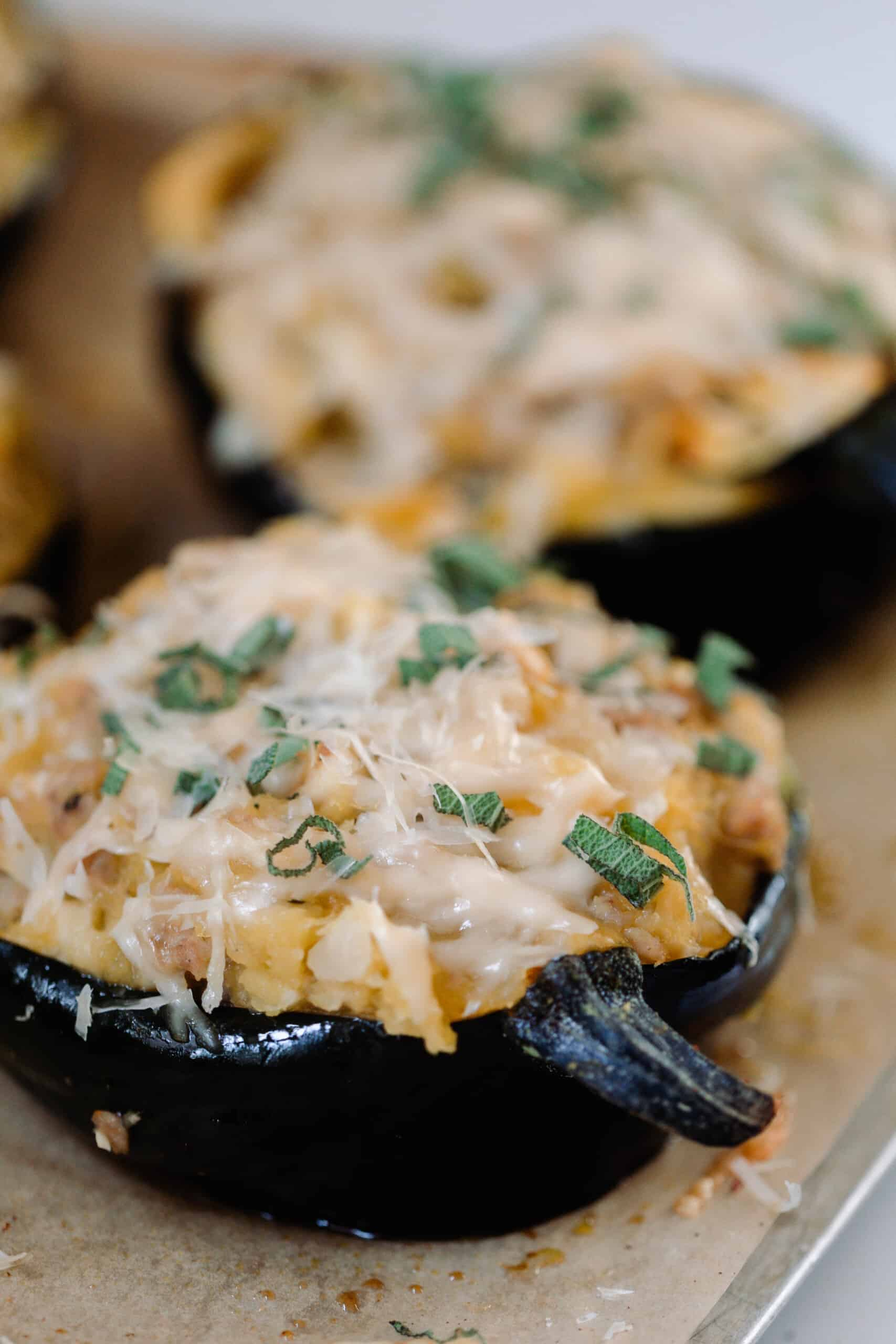 two stuffed acorn squashes topped with cheese on a wood cutting board