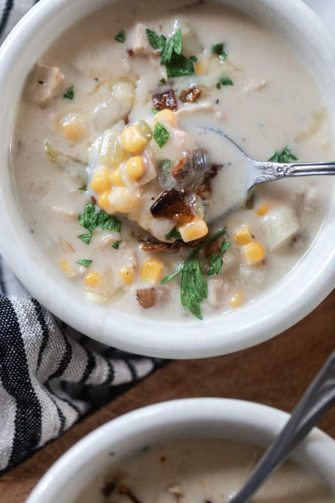 white bowl of creamy chicken and corn chowder with bacon with a spoon in the bowl of soup. Another bowl of soup is right in front resting on a cutting board