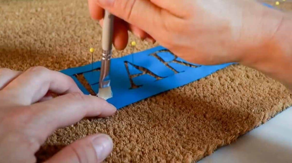 hands using a paintbrush to pain on a blue stencil on a welcome mat