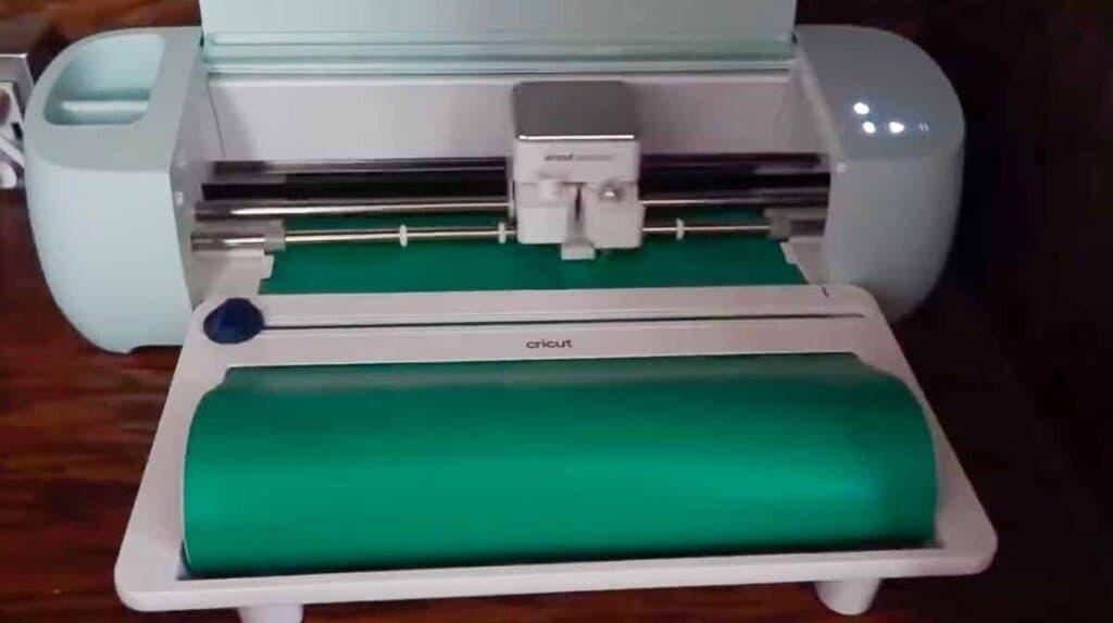 Cricut cutting out a design on green vinyl