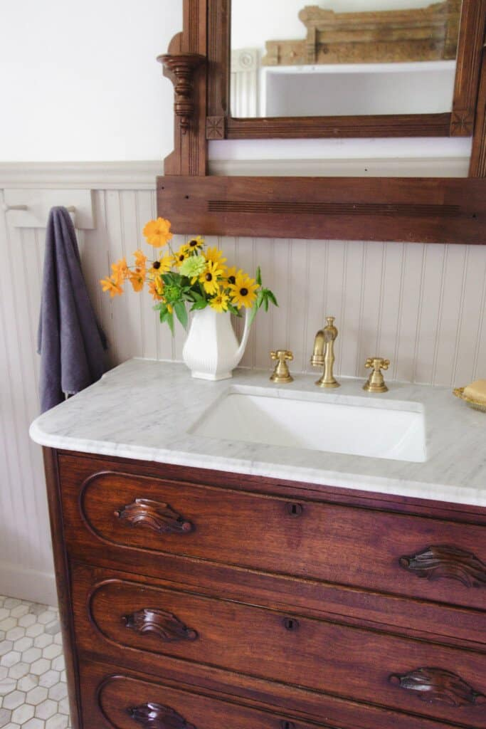 1800's farmhouse bathroom with a antique marble top dresser turned into a bathroom vanity with brass fixtures. A antique mirror hangs above the sink
