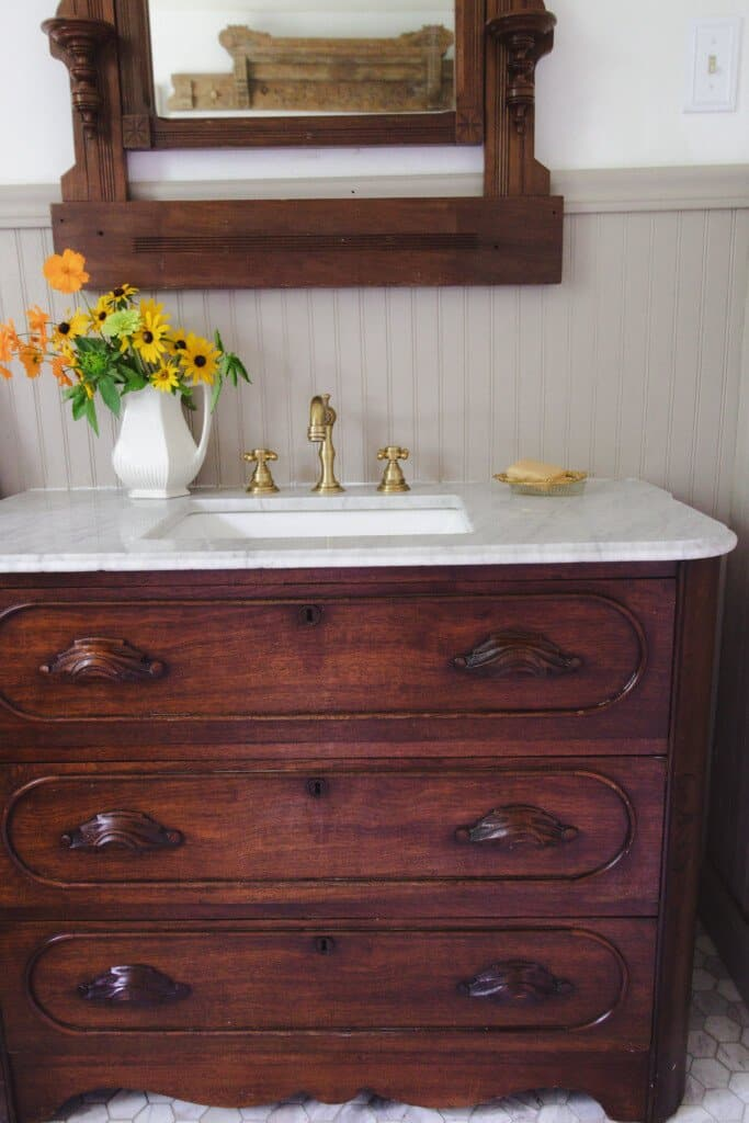 an antique dresser turned into vanity with marble countertop, brass faucets, and flowers.