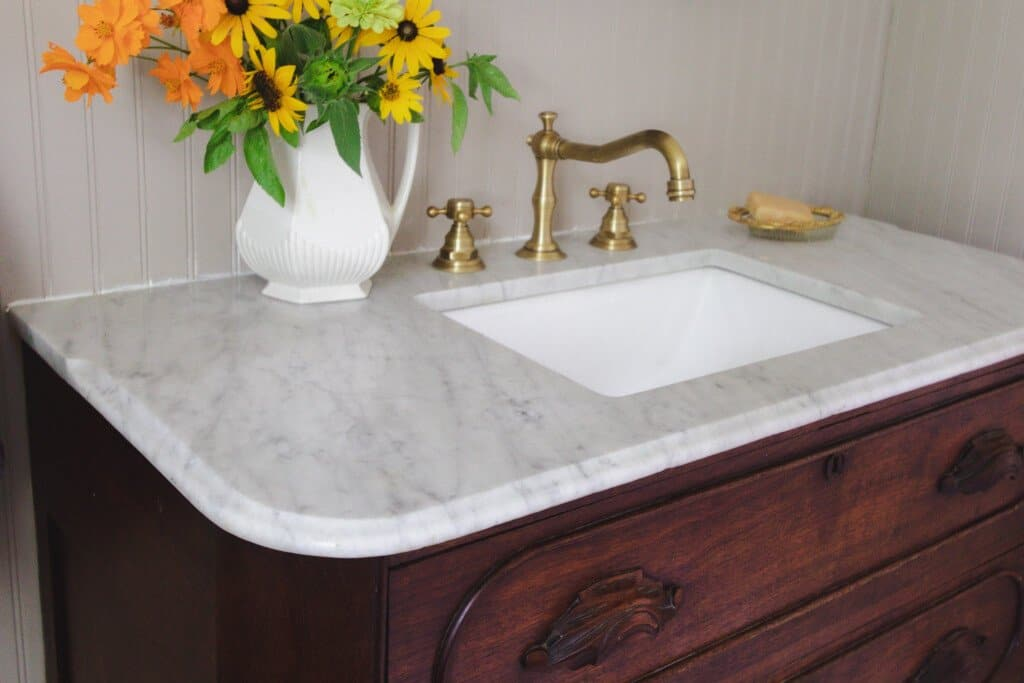 side view of a wood dresser with marble top turned into a vanity with brass faucet. A vase of flower sits to the left of the sink and a brass soap dish to the right