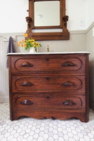 stained wooden antique dresser turned into a bathroom vanity with a marble top. A antique mirror hangs over the vanity.