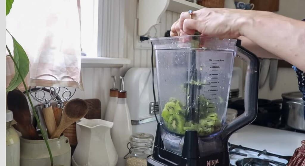 women squeezing a lime into a blender with kiwi in the blender