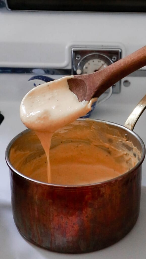 pumpkin pasta sauce in a copped pot with a wooden spoon scooping out the sauce and allowing it to drip back into the pan