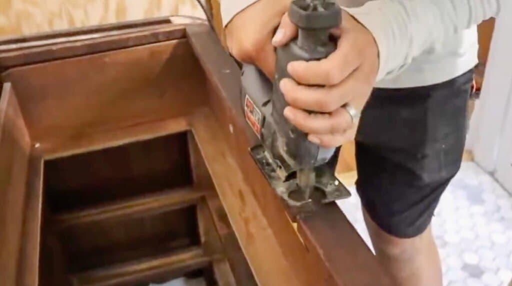 jigsaw cutting out a notch out of a dresser to accommodate a sink