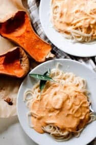 two plates our pumpkin squash pasta sauce over spaghetti with two halves of butternut squash to the side