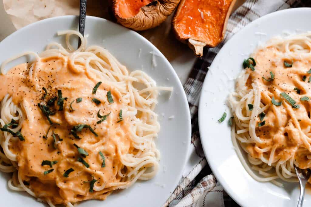 two light gray plates with spaghetti with butternut squash pasta sauce and sage over the spaghetti