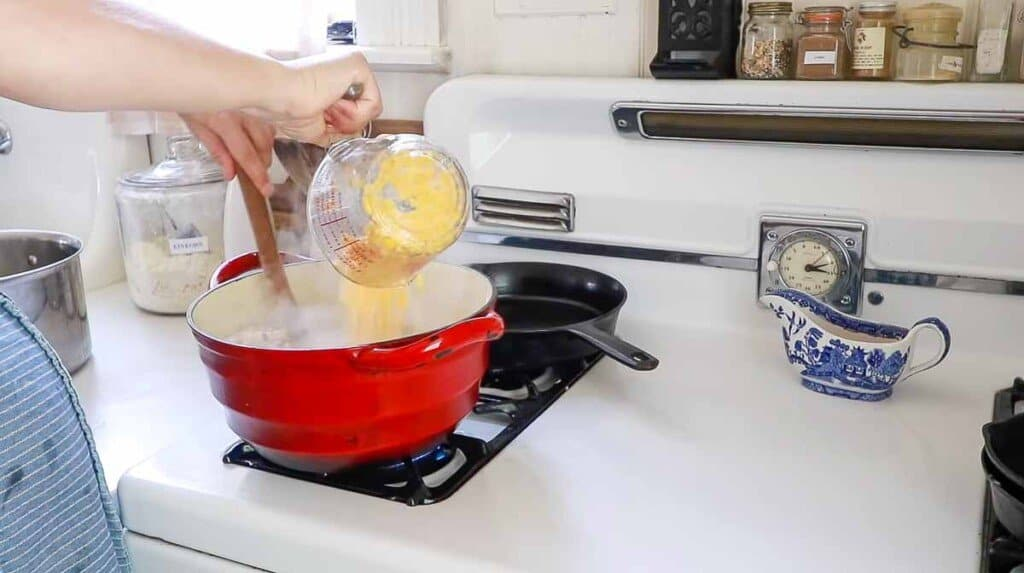 corn in a liquid measuring cup being added to chicken corn chowder in a red dutch oven on a white vintage stove