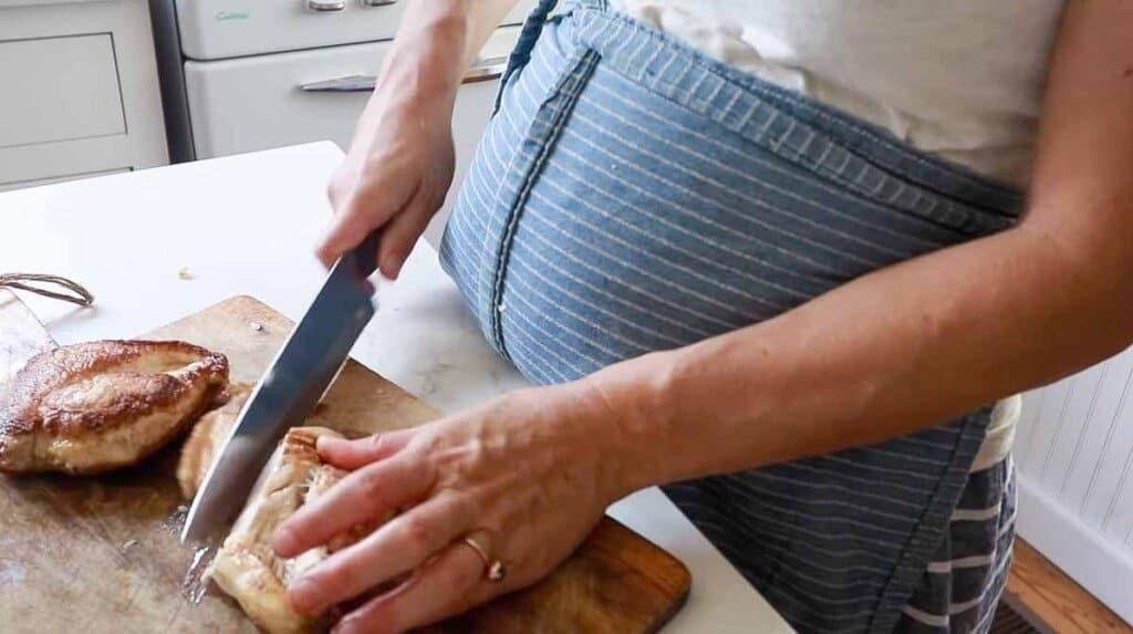 women wearing a blue apron slicing seared chicken on a wood cutting board