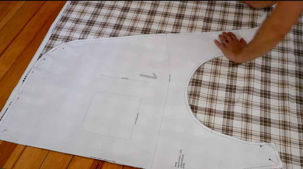 apron pattern laid on a piece of folded plaid fabric