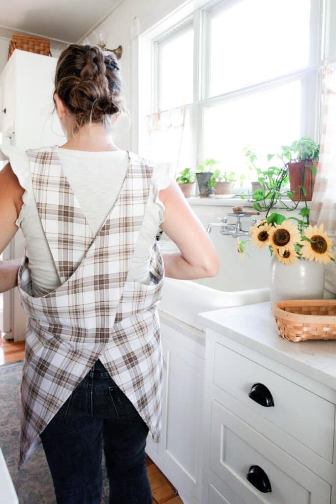 A women wearing and showing the back of a cross-back apron made of brown and beige plaid fabric in a white victorian kitchen