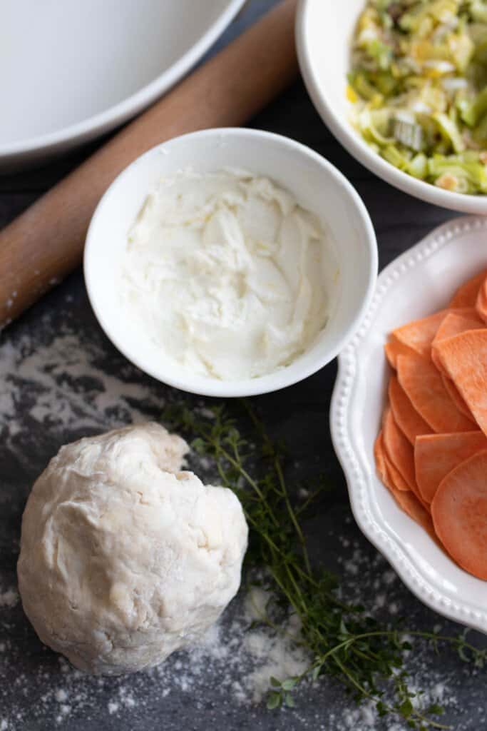sourdough leek and sweet potato galette ingredients in bowls on a countertop with a rolling pin