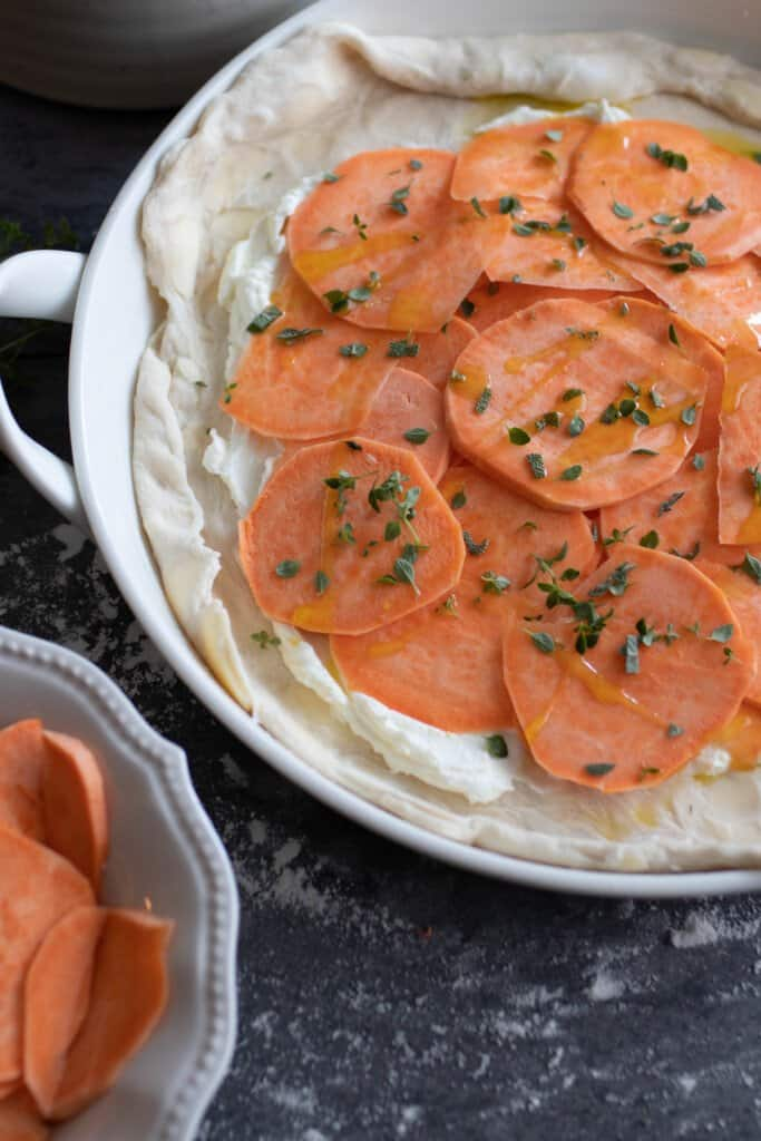 sliced sweet potatoes on top of a goat cheese spread on pie crust in a baking dish