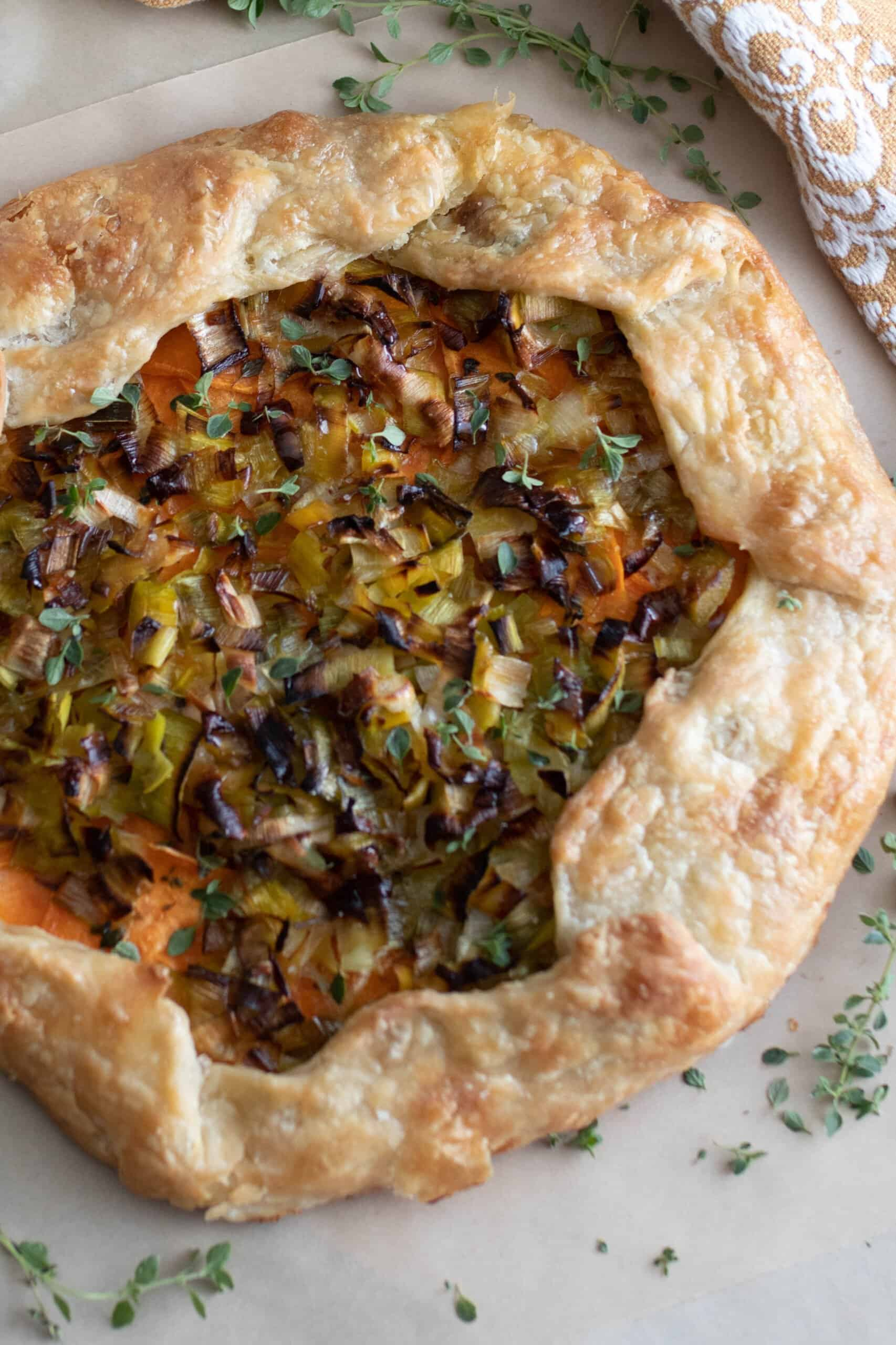 overhead photo of a sourdough galette with leeks and sweet potatoes on a marble countertop with herbs sprinkled around
