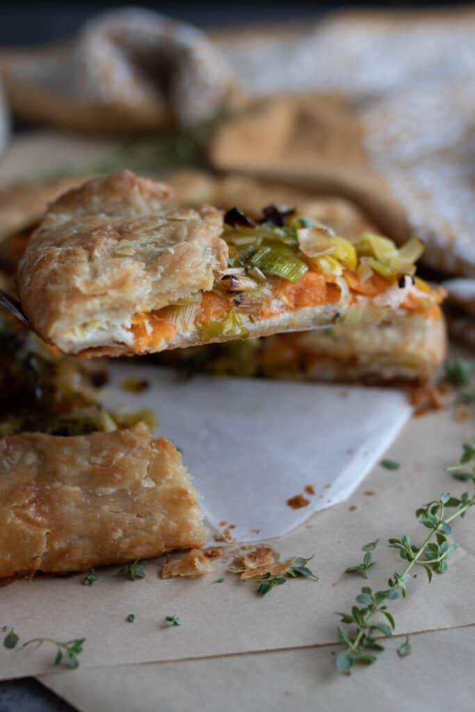side view of a slice of sourdough galette with leeks and sweet potatoes with the rest of the galette in the background