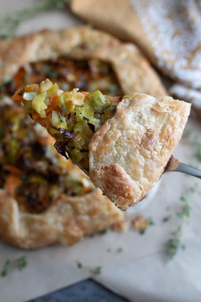 sourdough galette with sweet potatoes, leeks, goat cheese and herbs with a slice cut out and being lifted up